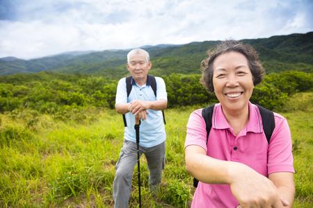 old couple walking: happy senior couple hiking on the mountain Stock Photo