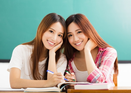 Two  happy teenage students girls in classroom Stock Photo
