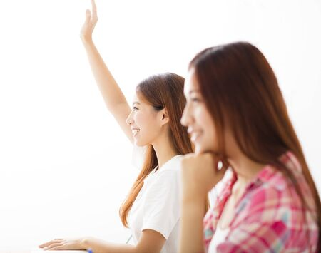 raising: happy young student  raised hands in class