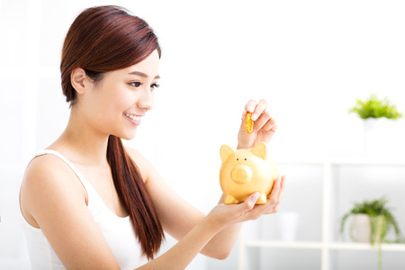 woman holding money: Happy young woman saving money in the piggy bank