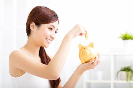 dinero: Mujer joven feliz que el ahorro de dinero en la alcancía
