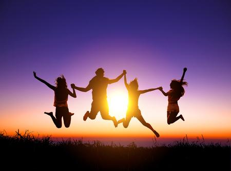 gruppo di giovani felici che saltano sulla montagna Archivio Fotografico