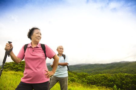 happy asian people: happy senior couple hiking on the mountain Stock Photo