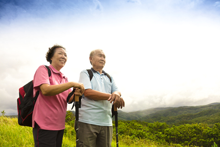 asian old man: happy senior couple hiking on the mountain Stock Photo