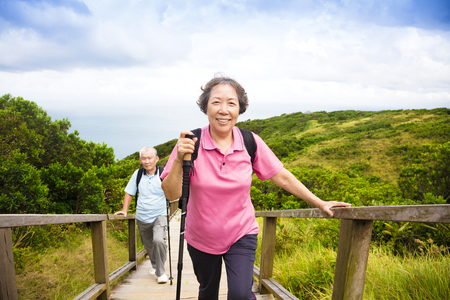 old man walking: happy senior couple hiking on the mountain Stock Photo