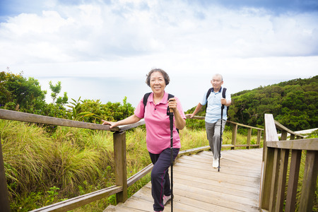 couple relaxing: happy senior couple hiking on the mountain park
