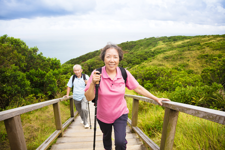 active woman: happy senior couple hiking on the mountain park