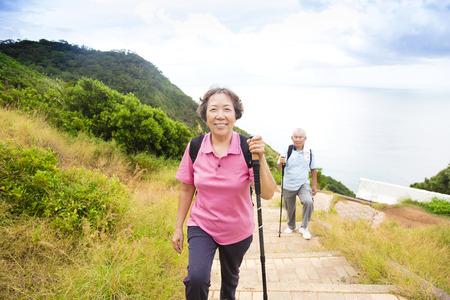 persona alegre: feliz pareja de senderismo mayor en el parque de monta�a