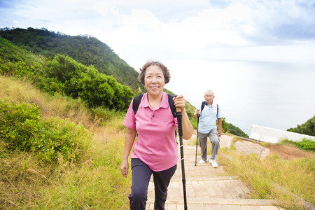 senior exercise: happy senior couple hiking on the mountain park