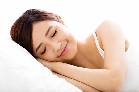 femmes souriantes: belle jeune femme dormir sur le lit Banque d'images