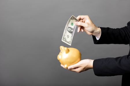 dollaro: business man  putting cash dollars into  piggy bank Archivio Fotografico