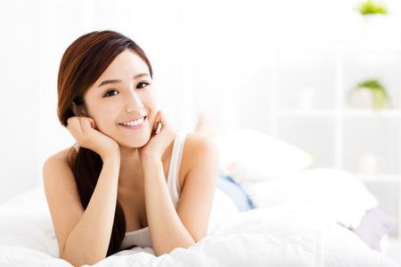 cheerful woman: joven y bella mujer asi�tica en la cama Foto de archivo