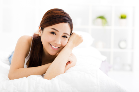 happy asian people: smiling young asian woman  on the bed
