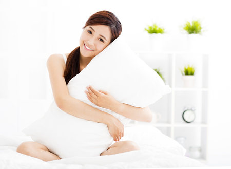 cama: mujer asiática joven sonriendo en la cama