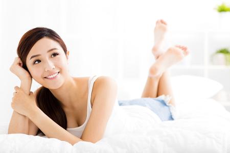 s úsměvem: krásná mladá žena asijských na posteli
