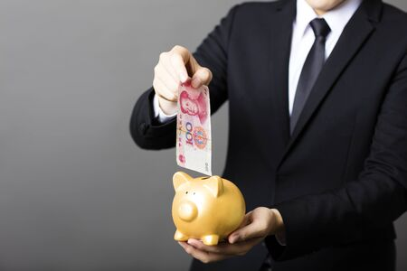 invest: business man  putting cash yuan into  piggy bank Stock Photo