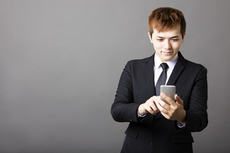 businessman phone: young businessman checking message on the phone