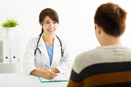 persona enferma: mujer médico hablando con el paciente en el consultorio