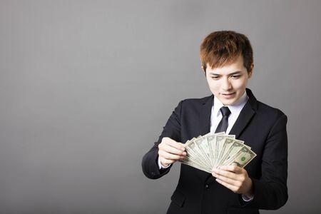counts: happy young businessman counts dollar  money in hands