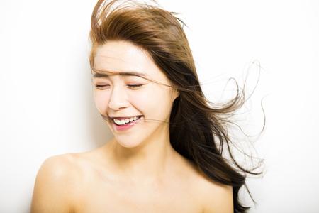 Mujer joven con el movimiento del cabello en el fondo blanco