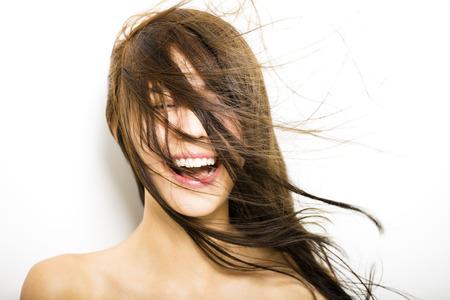 s úsměvem: Mladá žena s vlasy pohybu na bílém pozadí