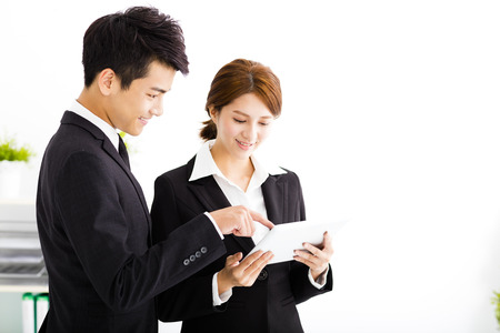 business partners looking at business document in tablet Stock Photo