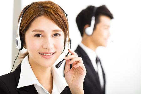 mujer trabajadora: j�venes empresarios que trabajan con auriculares en la oficina Foto de archivo