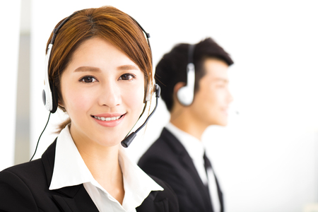 businessman smiling: young business people working with headset in office