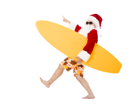 tropical christmas: Happy Santa Claus holding surf board with pointing gesture