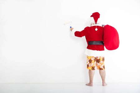 beachwear: santa claus with beachwear and painting on the white wall