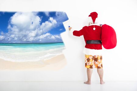 beachwear: santa claus with beachwear and painting vacation concept on the wall Stock Photo