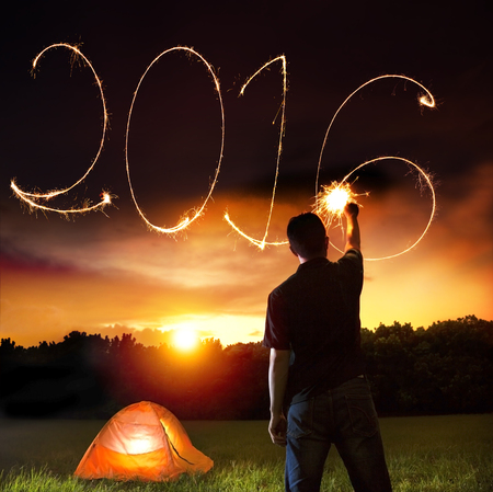 happy new year 2016.young man drawing by sparkler photo
