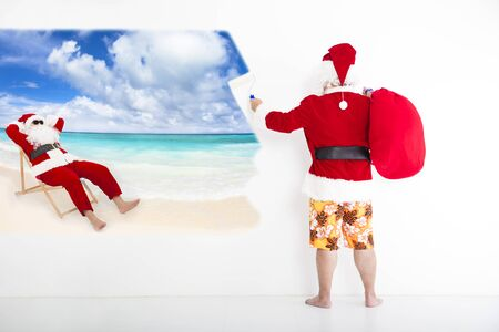 beachwear: santa claus with beachwear and painting vacation concept on wall Stock Photo