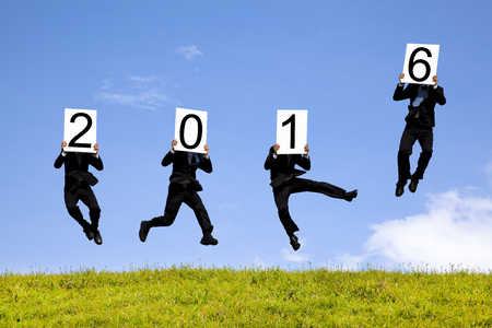 businessman showing new year 2016 and jumping on the grass photo