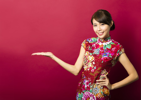 cheongsam: smiling young chinese woman with showing gesture