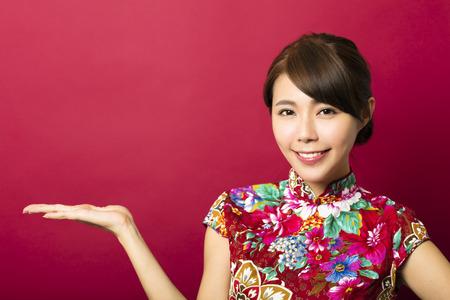lächelnde junge chinesische Frau mit zeigt Geste