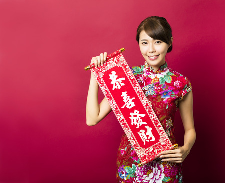 young asian woman showing Spring festival couplets for chinese new year