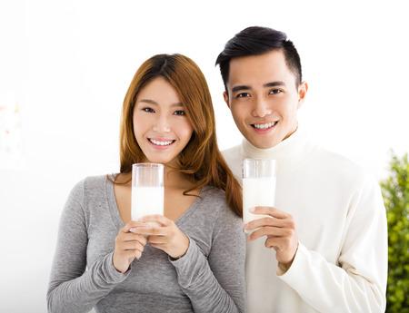 držení: Mladé krásné usměvavé dvojice konzumní mléko