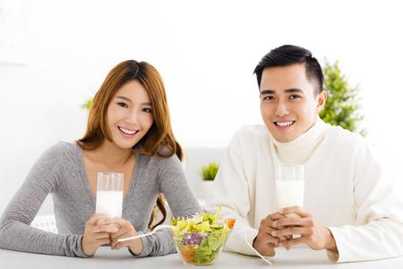 젊은 아름 다운 미소 커플 우유를 마시는