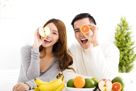 здравоохранение: счастливая молодая пара едят фрукты и здоровое питание