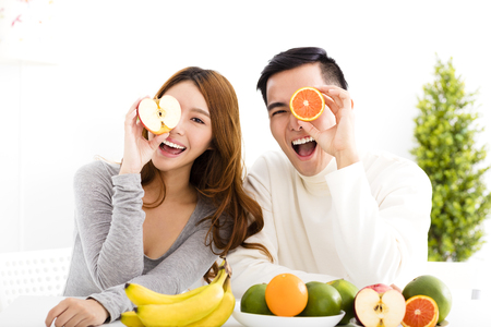 Esposas: feliz pareja joven comer frutas y alimentos saludables