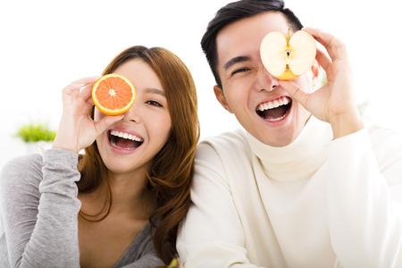estilo de vida: Casal jovem feliz que mostra o alimento saudável