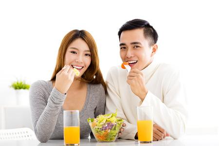 pareja comiendo: El par sonriente joven que come el alimento sano
