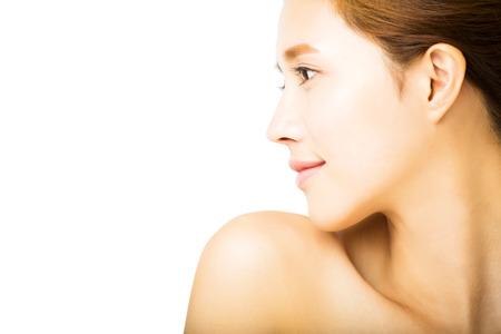 shoulders: vista lateral de la mujer sonriente joven con la cara limpia