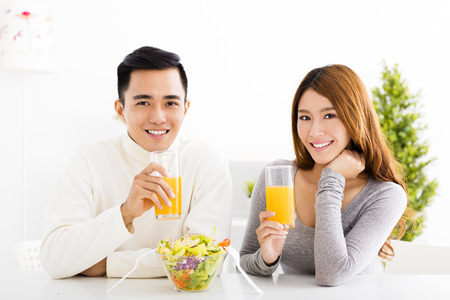 Young  smiling couple drinking juice and healthy food Zdjęcie Seryjne