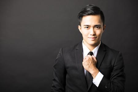 jonge Aziatische zakenman op een zwarte achtergrond Stockfoto