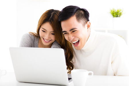 asian on laptop: happy Asian Couple Looking at Laptop In living room