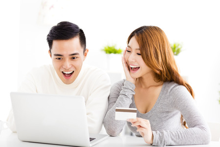 happy family shopping: happy young couple with credit card and  laptop Stock Photo