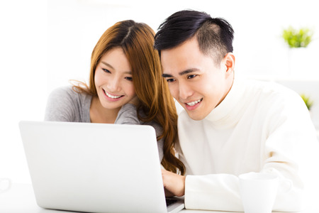 laptop computer: happy Asian Couple Looking at Laptop In living room