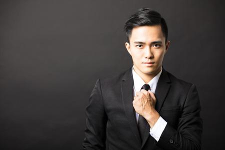 viso uomo: giovane uomo d'affari asiatico su sfondo nero Archivio Fotografico